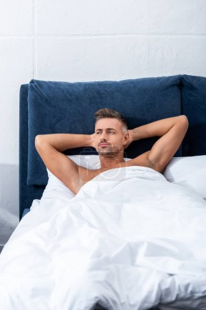 Photo for Pensive adult man laying in bed and looking away at home - Royalty Free Image