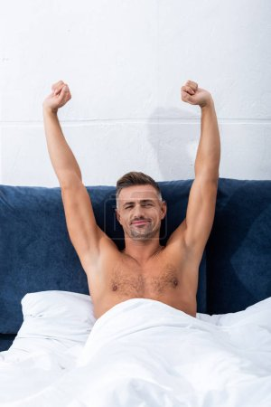 Photo for Happy shirtless man with raised arms laying in bed at home - Royalty Free Image