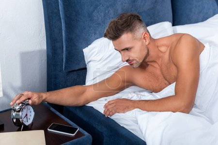 selective focus of man turning off alarm clock during morning time at home