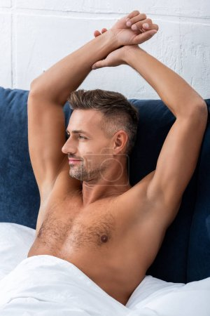 Photo for Portrait of happy shirtless man with raised arms laying in bed at home - Royalty Free Image