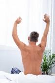 """Постер, картина, фотообои """"вид сзади рубашки человека растяжения сидя на кровати во время утром у себя дома"""""""