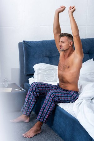 Photo for Shirtless happy man with raised arms sitting on bed at home - Royalty Free Image