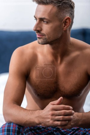 thoughtful shirtless man sitting on bed and looking away at home
