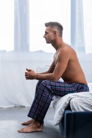 Photo for Side view of shirtless man sitting on bed during morning time at home - Royalty Free Image