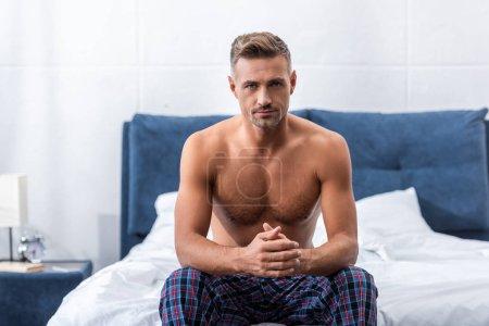 selbstbewusster erwachsener Mann ohne Hemd, der in die Kamera schaut und zu Hause auf dem Bett sitzt