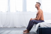 side view of adult man sitting on bed during morning time at home