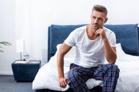 Photo pour Homme adulte pensif, assis sur le lit pendant une heure du matin à la maison - image libre de droit