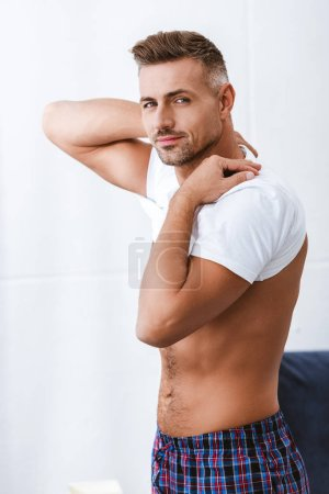 handsome adult man looking at camera and putting on white t-shirt at home