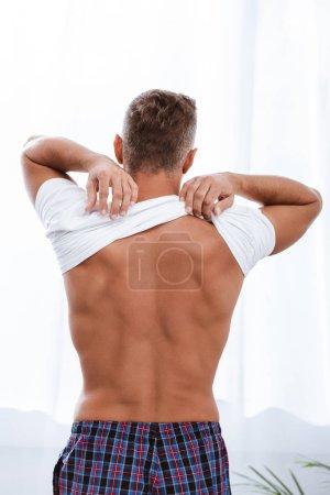 Photo pour Arrière de l'homme mettant sur t-shirt blanc tout en étant assis sur le lit à la maison - image libre de droit