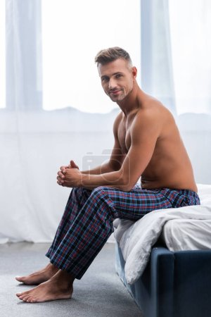 Photo for Smiling shirtless adult man sitting on bed during morning time at home - Royalty Free Image