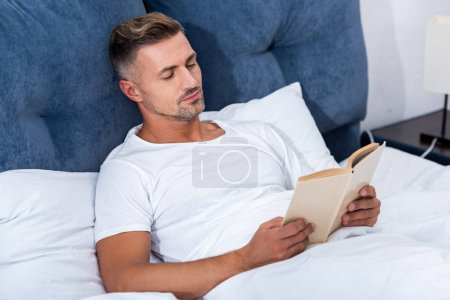 Photo for Adult man reading book while laying in bed at home - Royalty Free Image