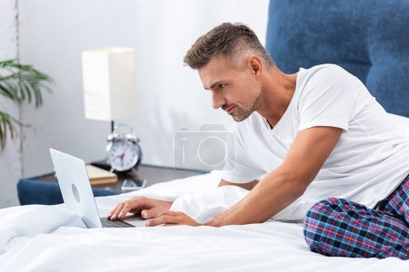 Photo for Adult male freelancer laying in bed and using laptop during morning time at home - Royalty Free Image