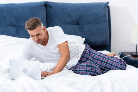 Photo for Happy adult male freelancer laying in bed and using laptop during morning time at home - Royalty Free Image