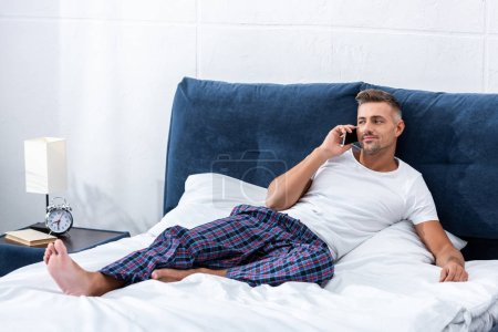 Photo for Cheerful adult man talking on smartphone while laying in bed at home - Royalty Free Image