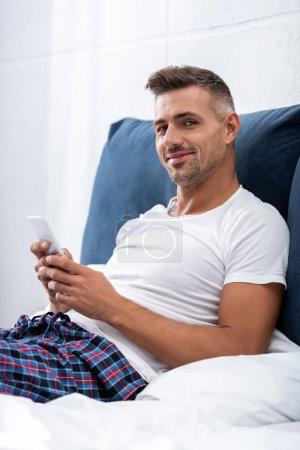 homme souriant en t-shirt blanc, regardant la caméra et à l'aide de smartphone dans le lit à la maison
