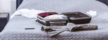 Photo for Wheeled bag, clothes and smartphone on bed at home - Royalty Free Image