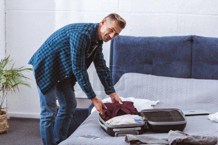 Photo pour Souriant voyageur masculin emballage des bagages dans la chambre à coucher à la maison - image libre de droit
