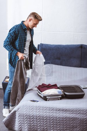 Photo for Handsome adult male traveler packing luggage in bedroom at home - Royalty Free Image