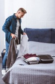 handsome adult male traveler packing luggage in bedroom at home