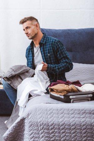 Photo pour Homme réfléchi assis avec des vêtements près sac à roulettes dans la chambre à coucher à la maison - image libre de droit