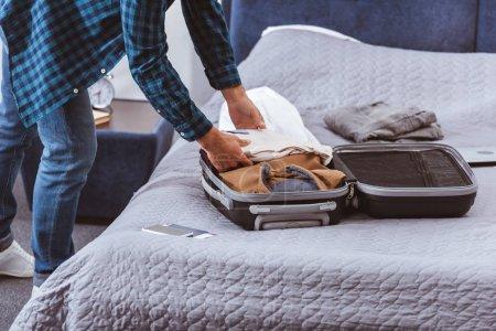 Photo pour Image recadrée du voyageur masculin emballant des bagages dans la chambre à coucher à la maison - image libre de droit