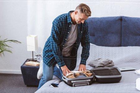 Photo pour Adulte voyageur homme emballage des bagages dans la chambre à coucher à la maison - image libre de droit