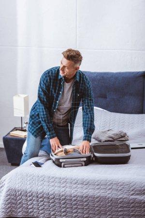 Erwachsener Mann packt Handtasche zu Hause im Schlafzimmer ein