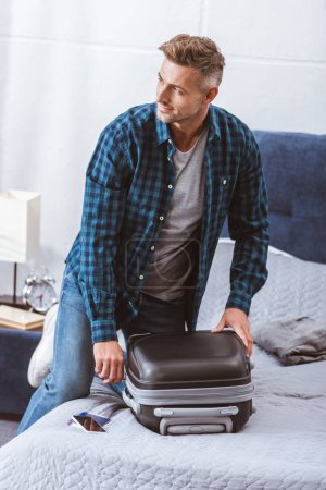 Photo for Man packing travel bag and looking away in bedroom at home - Royalty Free Image
