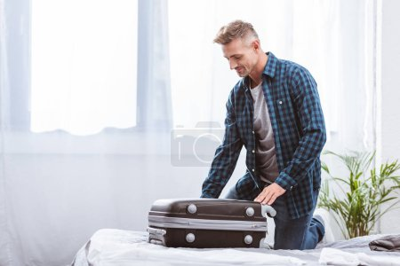 Photo pour Joyeux voyageur masculin sac de voyage dans la chambre à coucher à la maison - image libre de droit