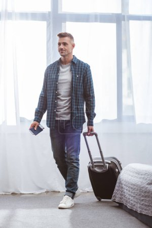 man with passport and flight ticket carrying travel bag at home