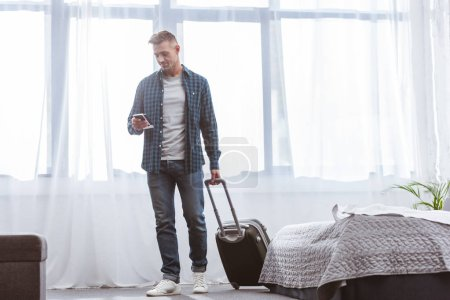 cheerful man using smartphone and carrying wheeled bag at home