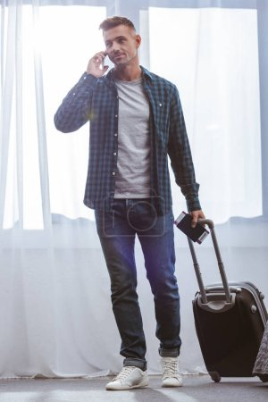 adult male traveler with passport carrying wheeled bag and talking on smartphone at home
