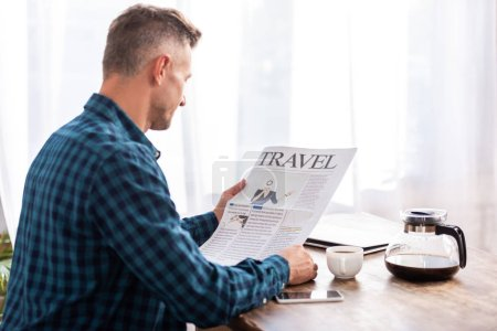 rear view of man sitting at table and reading travel newspaper in kitchen at home