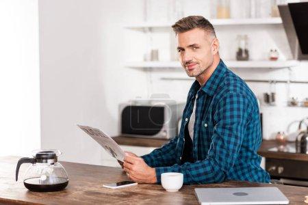 Photo pour Bel homme en chemise à carreaux lisant le journal de voyage et souriant à la caméra - image libre de droit