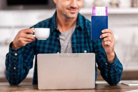 Photo pour Plan recadré d'un homme souriant tenant une tasse de café et un passeport avec carte d'embarquement tout en utilisant un ordinateur portable à la maison - image libre de droit