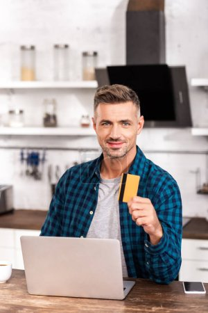 handsome man holding credit card and smiling at camera while using laptop at home