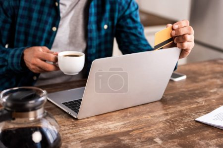 close-up partial view of man holding cup of coffee and credit card while using laptop at home