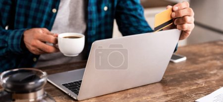 cropped shot of man holding cup of coffee and credit card while using laptop at home