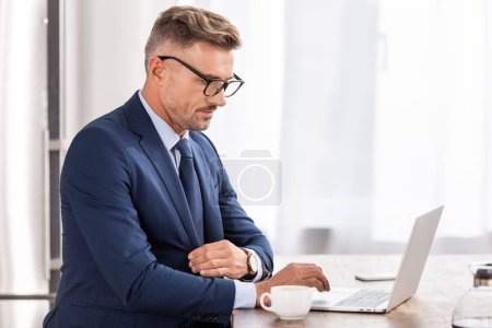 Photo for Handsome businessman in formal wear and eyeglasses using laptop at home - Royalty Free Image