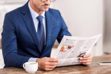 Foto de Recortar el tiro del empresario en el juego leyendo el periódico por la mañana - Imagen libre de derechos