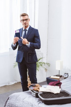 Photo for Handsome businessman holding passport with boarding pass and looking at camera while packing suitcase at home - Royalty Free Image