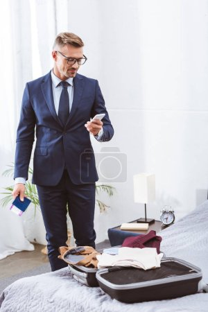 Photo for Smiling businessman in suit and eyeglasses holding passport with boarding pass and using smartphone while packing suitcase at home - Royalty Free Image