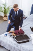 high angle view of man in suit and eyeglasses using smartphone and packing suitcase for business trip