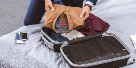 Photo for Partial view of businessman in suit packing suitcase on bed - Royalty Free Image