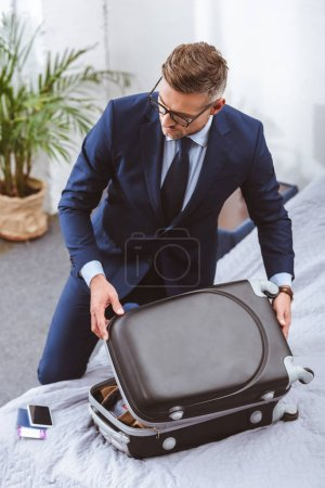 Photo for High angle view of businessman in suit and eyeglasses packing suitcase at home - Royalty Free Image