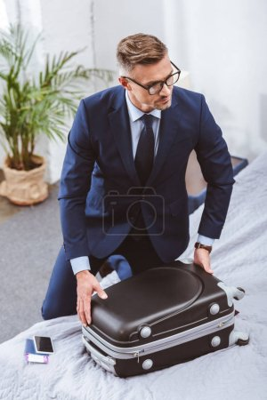 high angle view of businessman in suit and eyeglasses packing suitcase and looking away at home