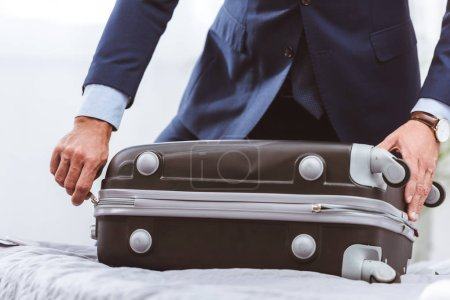 Photo for Cropped shot of businessman in suit packing suitcase on bed - Royalty Free Image