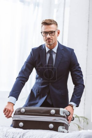 Photo for Handsome businessman in suit and eyeglasses packing suitcase and looking at camera - Royalty Free Image