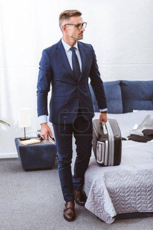 Photo pour Homme d'affaires en tenues tenant valise et à la recherche de suite à domicile - image libre de droit