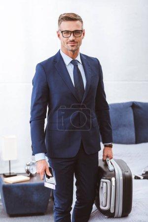 Foto de Apuesto empresario sonriente sosteniendo la maleta, pasaporte con billete y smartphone - Imagen libre de derechos